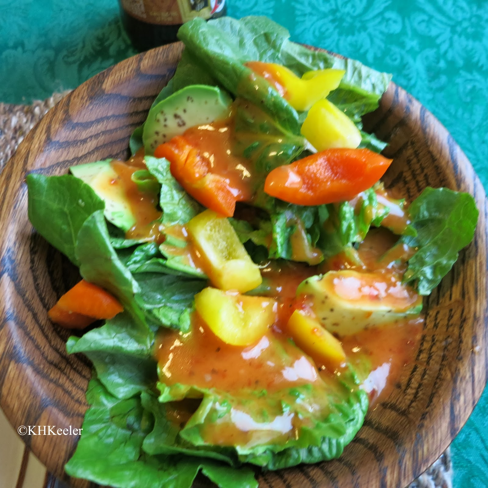 green salad with avocado, peppers and roasted red pepper dressing