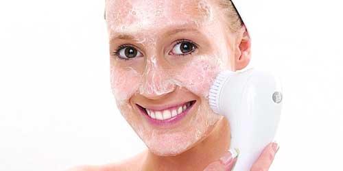 chica usando el cepillo de limpieza del rostro