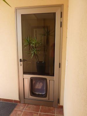 vista exterior de puerta aluminio con trampilla para mascotas