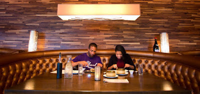 Two people eating at a restaurant booth