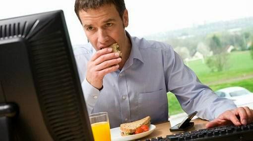 دراسة تكشف العلاقة بين العمل المكتبي وزيادة الوزن - رجل يأكل جالس يجلس على مكتب كمبيوتر