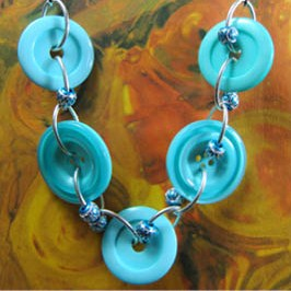 Necklace has big teal buttons and small accent beads connected with silver loops