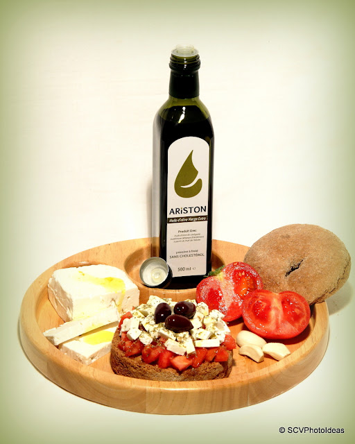 Ariston Olive oil bottle in wooden plate w/ tomato-feta cheese-cracker