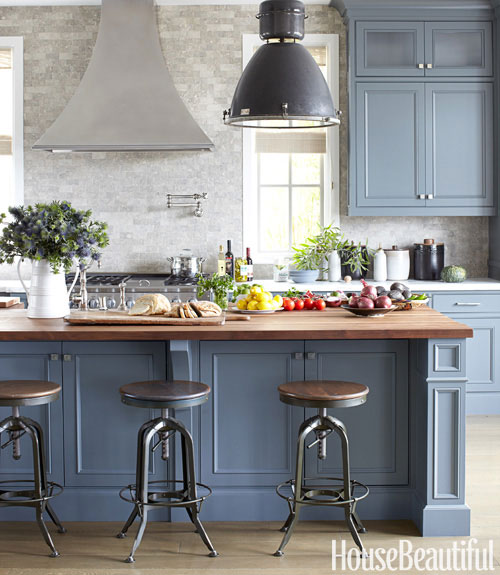 kitchen with black pendant lights, blue grey cabinets, turn stools, butcher island and tumbled marble backsplash