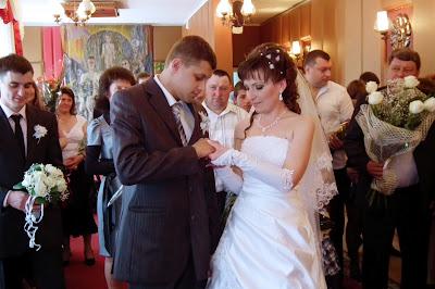 Свадебное фото - невеста одевает жениху обручальное кольцо