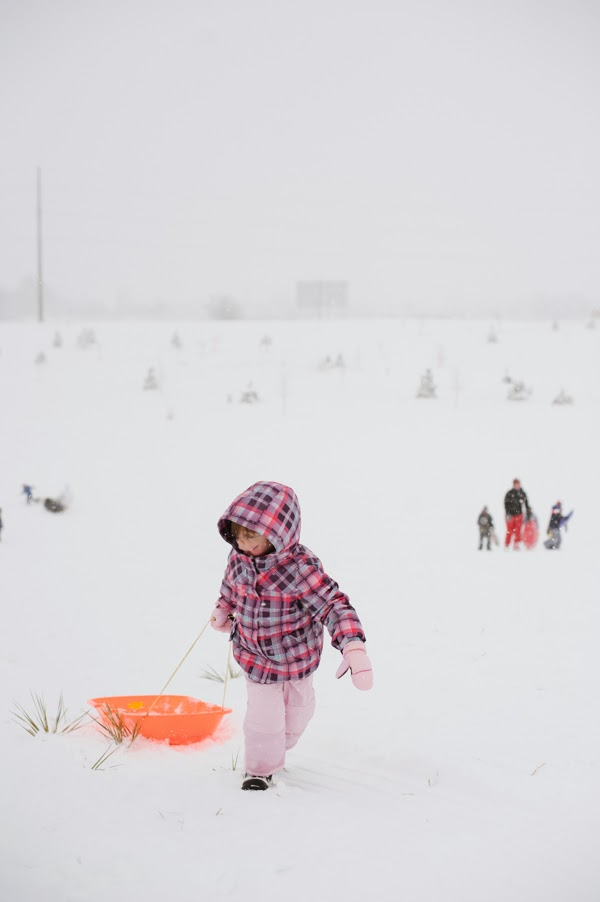 girl pulling orange sled up a big snowy hill