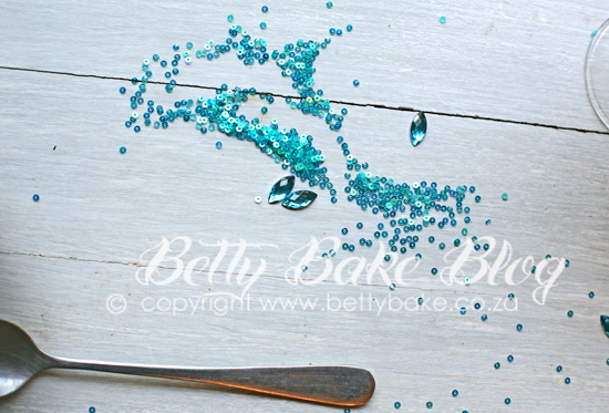 betty bake, sparkly, sequines, turquoise, spoon, on grey and white