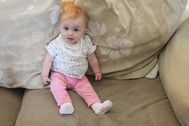 baby wearing cat print t-shirt and pink corduroy trousers