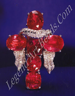 A pink sapphire cross with diamond encrusted scarf-representing Veronica's Veil.