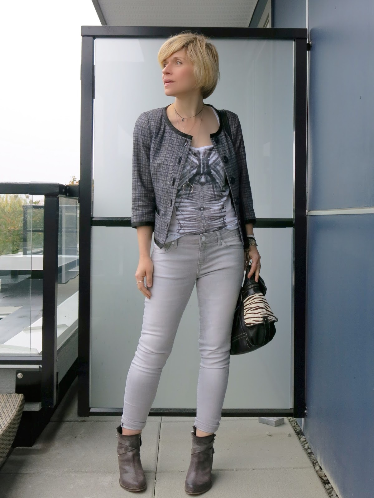 styling grey skinny jeans with a Chanel-style jacket and ankle booties
