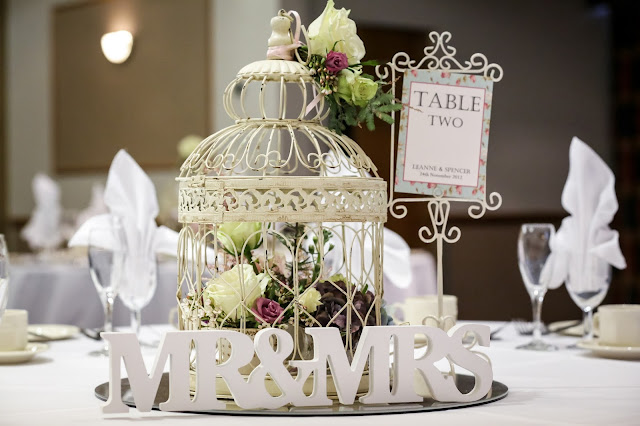 vintage themed wedding table decorations birdcage filled with vintage cups & saucers and flowers, Mr & Mrs Sign and floral table numbers signs