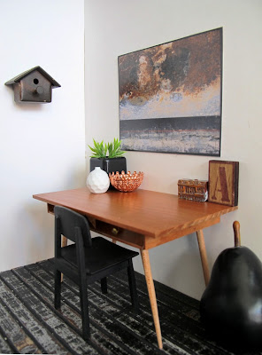 Modern miniaturecorner of a room with a mid-century modern wooden desk and chair, a large pear on the floor and a birdhouse on the wall.