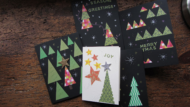 5 handmade christmas cards laying on a wooden table
