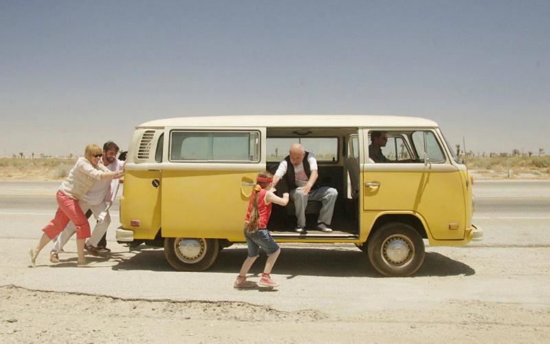 Na imagem: Cena de Little Miss Sunshine com uma kombi amarela e branca parada na beira da estrada, atrás um homem e uma mulher empurrando, a porta lateral está aberta e um velhinho sentado no banco estica o braço pra pegar uma garotinha que tá correndo pra pular dentro