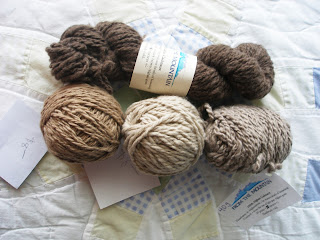 4 small skeins of cashmere yarn in dark brown, tan, beige, and cream from Afghani women