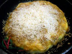 Cuajar la tortilla por el otro lado y dejar fundir el queso rallado.