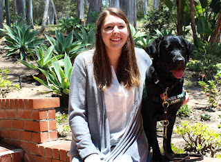 Christina smiles next to a black Lab guide dog puppy.