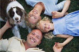 Smiling family lying on grass with their dog, build your life better, bigger, smarter