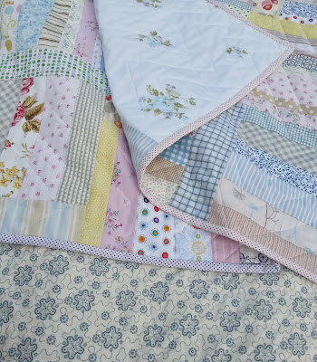 a close up picture of a folded quilt using only low volume fabrics