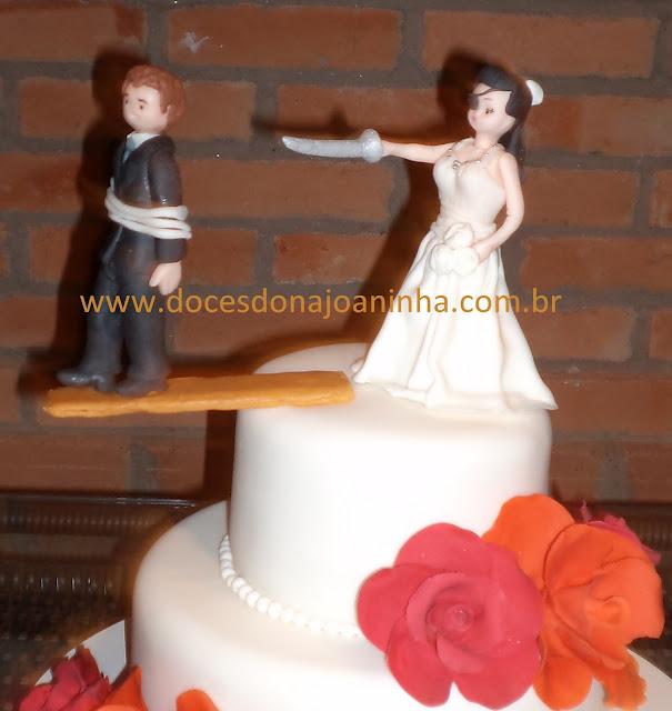 Bolo decorado de casamento com rosas de açúcar e topo de bolo noiva pirata e noivo na prancha