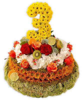 single layer cake covered in orange, red , and white flowers, and the number three