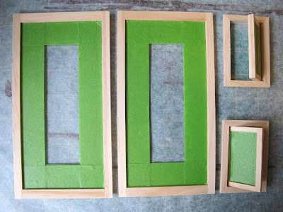 Four dolls' house miniature windows, taped ready for painting.