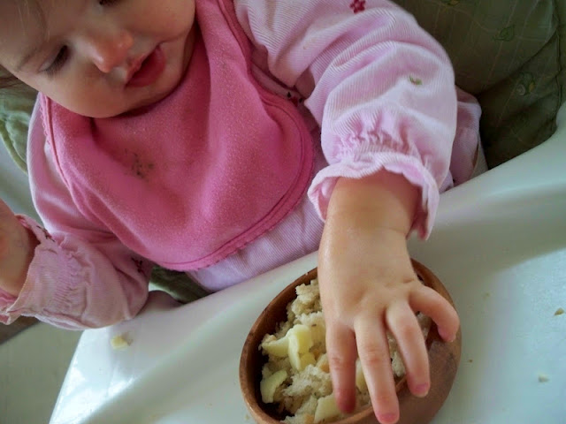 The baby eating from her wooden bowl