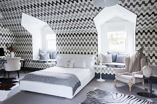Gwyneth Paltrow's bright guest apartment after makeover with a white bed, sitting area, desk and kitchenette