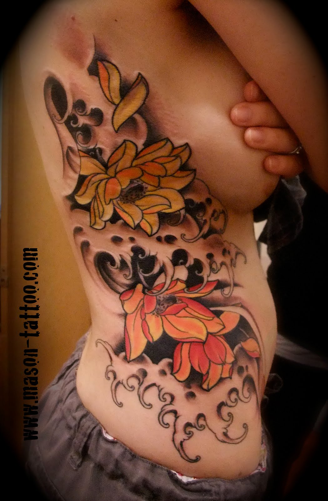 lotus flowers and waves tattoo on ribs