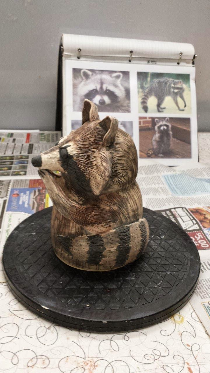 Cute thrown and handbuilt ceramic pottery raccoon garden sculpture.