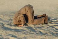 testa sotto la sabbia