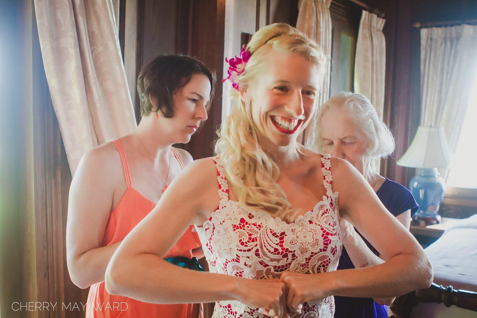 bride getting into wedding dress, mother of bride and maid of honour helping bride get into dress, happy moment, Thailand wedding, happy Thailand bride, destination wedding planning, Koh Samui destination wedding, Happy bride getting married on Koh Samui