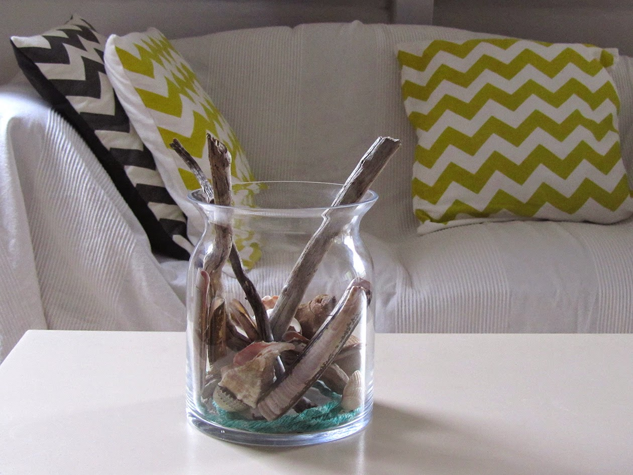 couch and glass jar with sea shells
