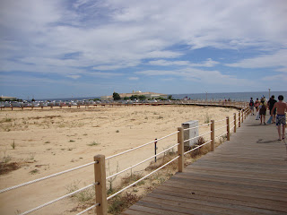 People in Salgados Beach wooden footbridge photo - Algarve