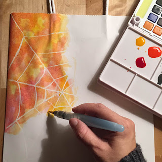 Painting beautiful orange yellow and red watercolors onto a white craft bag revealing a white spider web