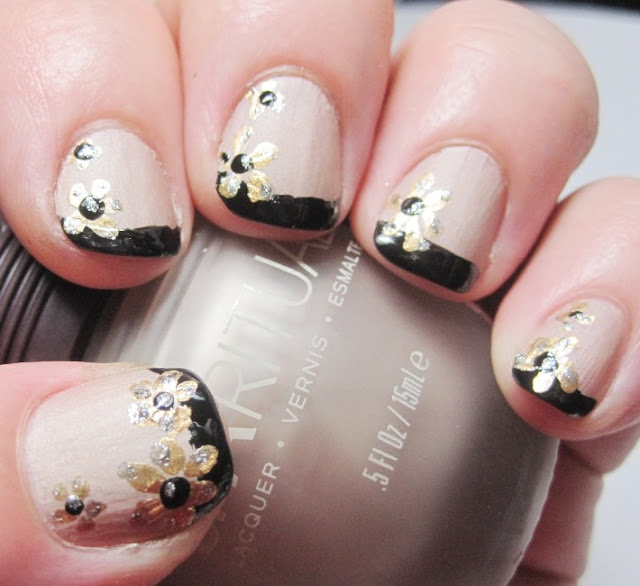 Gold flowers over a black French tip and nude nail