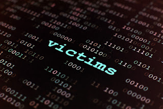 word victim among computer code, illustrating cybercrime.