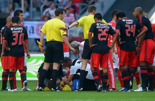 Referee Christian Fischer lies on the ground after he was attacked by Benfica captain Luisão
