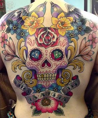 Tattoo de caveira mexicana com flores e pássaros nas costas