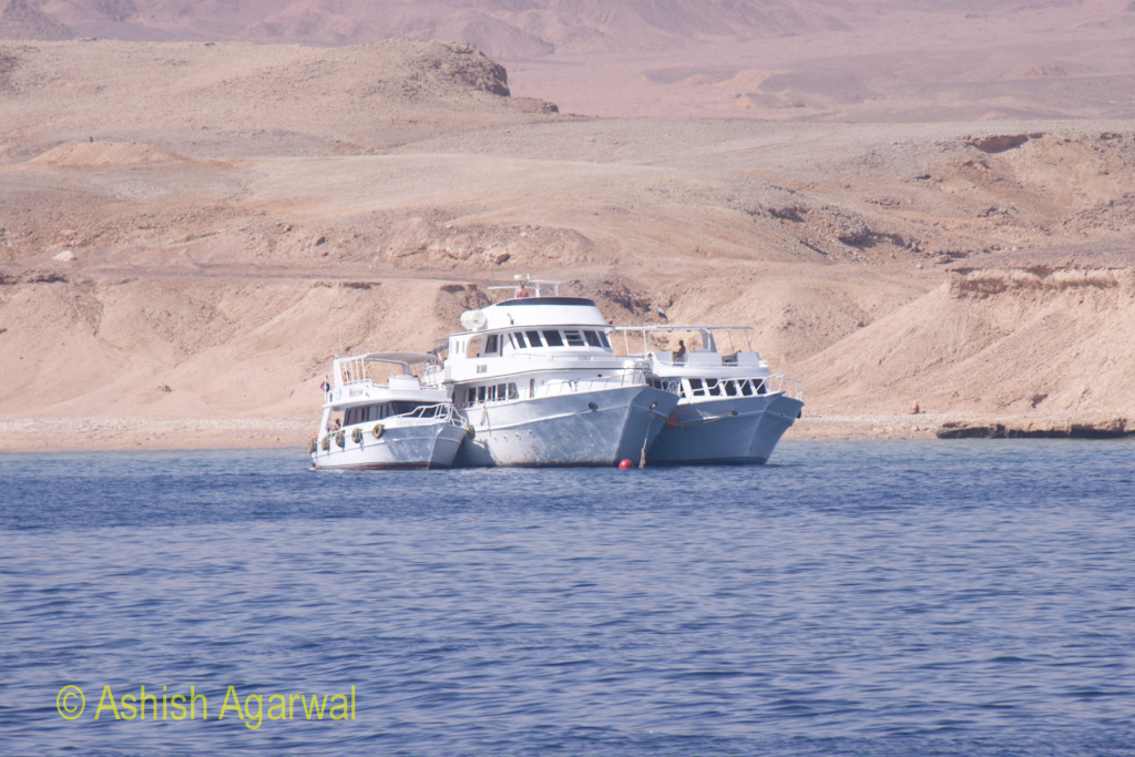 Multiple ships right next to each other with the shore in the background near Sharm el Sheikh