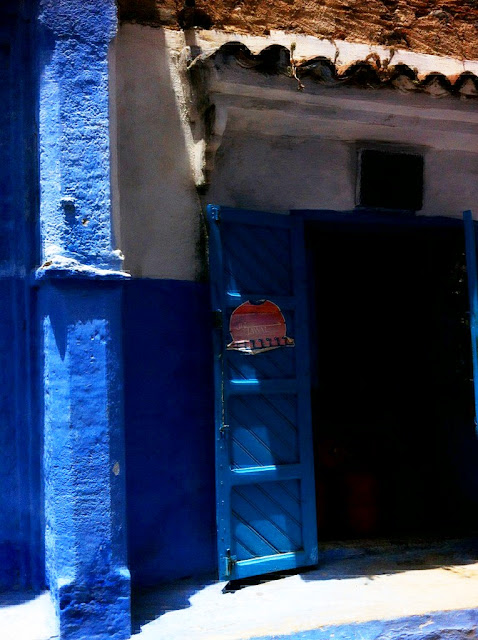 building with the lower half of the wall indigo blue, the upper half cream with blue doors in Morocco