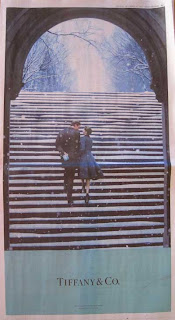 Full page newspaper ad for Tiffany & Co. with light turquoise, black and white color scheme, showing a young man and woman walking up a snowy staircase toward an arch with snow-covered trees