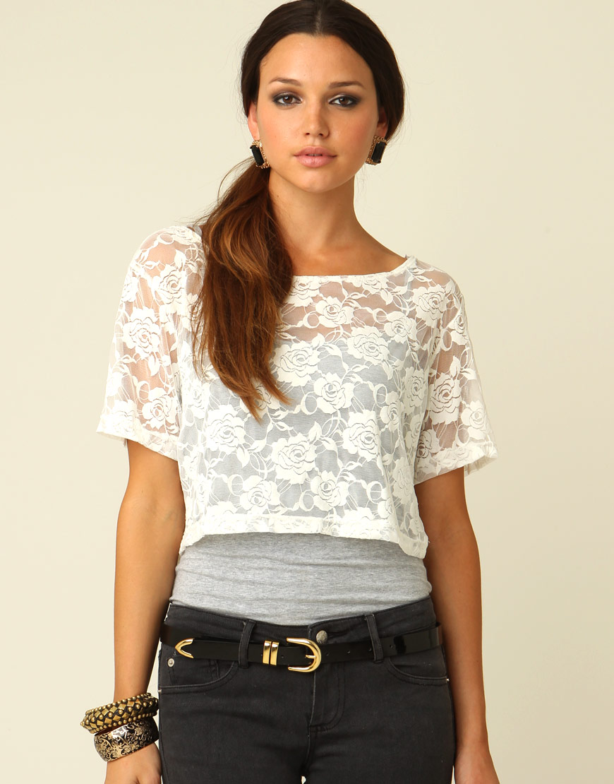 This flirty crop top features a high neckline, a lace-up front closure, and a colorful iridescent design. (Top only.).