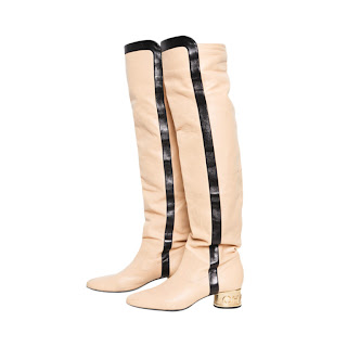 Vintage cream colored Chanel Go-Go boots with black and gold details.