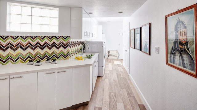 Angled wall in a laundry room with green, brown and white chevron printed backsplash