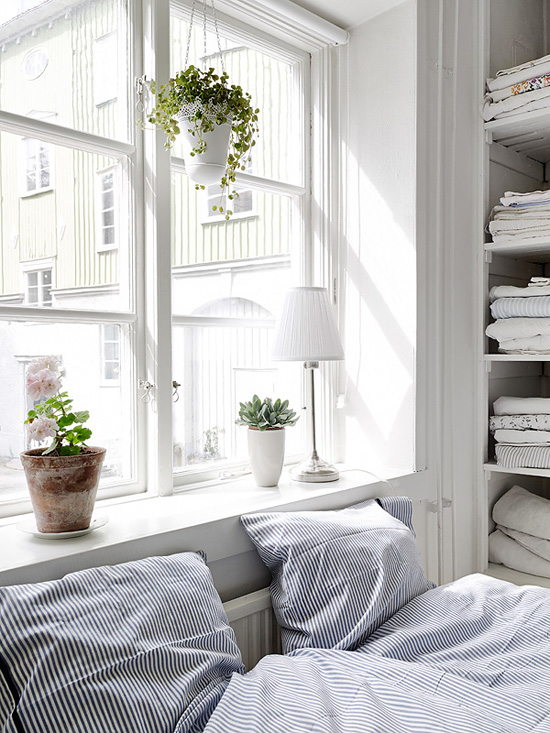 Bedroom with the bed located under the window and stripe linen set via Stadshem (via Sea of Girasoles)