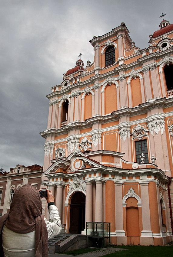 Vista integral da parte da frente da igreja. Uma mulher em primeiro plano, no canto inferior esquerdo, a tirar fotografias