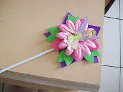 Un popote para globos pegado entre las hojas verdes y la flor rosa. (invitaci flor)