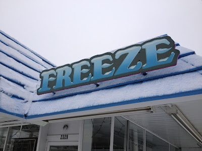 Blue-lettered sign reading FREEZE with snow on roof