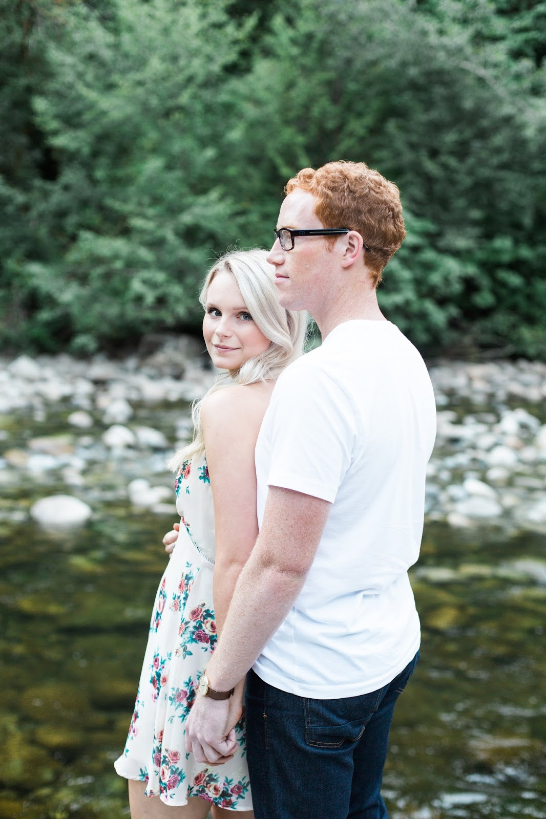 a blonde women looks back at the camera, water in the background, new fiance in the foreground, how to pose for engagement photos